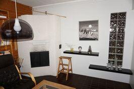 Takkahuoneessa takka ja lasitiiltä seinässä jonka takana sauna