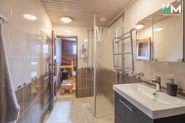 Tilava kylpyhuone on tyylikäs. Taustalla näkyy sauna.