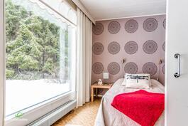 yksi kodin makuuhuoneista, joka on liukuovella erotettu olohuoneesta.
