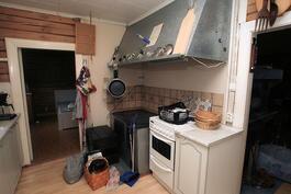 Keittiössä hella-uuni, liesikupu, ovi makuuhuoneeseen ja aukko tupaan