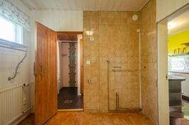 Kodinhoitohuone, josta kulku kylpyhuoneeseen