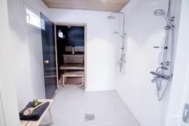 Tilavassa kylpyhuoneessa vaalean harmaa laatta, valkoiset kaakelit, tuplasuihkut ja led-valaisimet