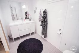 Kylpyhuoneessa vaaleat siistit pinnat, ikkuna, wc, suihku sekä lasinen suihkuseinä