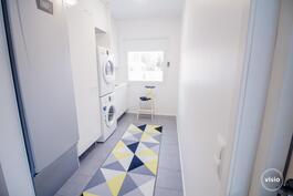 Harmaa laatta, maalatut seinät, pyykkikaappi, tilaa pesutornille sekä vesipiste ja pöytätaso