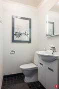Erillinen wc-tila, jossa tyylikkäät pintamateriaalit ja kalusteet.