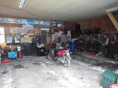 Erillinen autotalli, jossa voimavirta ja öljymonttu.