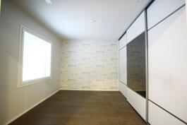 Makuuhuone koko seinän mittaisella liukuovikaapistolla