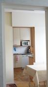 Yhdestä makuuhuoneesta näkyy ruokailutilan läpi keittiöön.