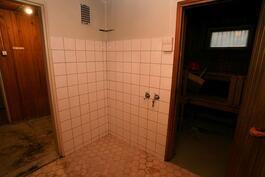 Kylpyhuoneesta vas. pukuhuoneeseen ja oik. saunaan