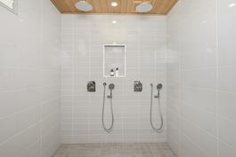 Kylpyhuoneessa seinään upotetut suihkut