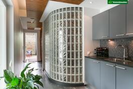 Takkahuoneessa on pieni avokeittiö ja lasitiiliseinän takana on saunaosasto