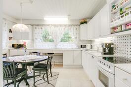 Vaaleasävyinen keittiö runsaalla kaappi- ja pöytätilalla.