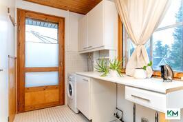 Kodinhoitohuoneeseen on käynti keittiöstä. Kuvassa ulko-ovi, josta pääsee suoraan suurelle takaterassille.