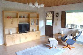Olohuone ja käynti koko talon sivun mittaiselle parvekkeelle.