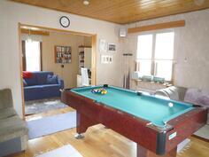 Avaran ja valoisan olohuoneen voi sisustaa vaikka biljardipöydällä.
