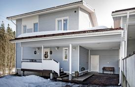 Taloa luoteen suunnasta, jossa katettu pääsisäänkäynti, autokatos ja lämmin varasto.