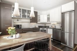 Keittiö ja ruokailutila. Kauniit ja laadukkaat kivitasot, rosteriset kodinkoneet ja ajattomat keittiökalusteet.