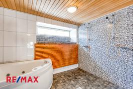 Kylpyhuoneessa kaksi suihkua ja poreamme