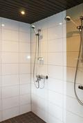laatoitettu pesuhuone, jossa kaksi suihkua