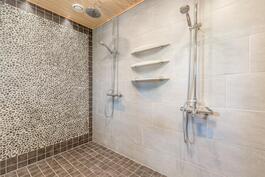 Pesuhuoneessa kaksi sadesuihkua ja näyttävä tehosteseinä