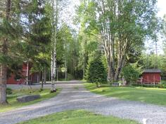 Avaraa ja aurinkoista piha-aluetta ympäröi suojaisa puusto