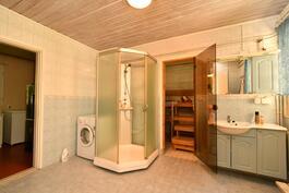Tilava kylpyhuonetila suikukaappeineen ja isoine saunoineen, vasemmalla kodinhoitotila