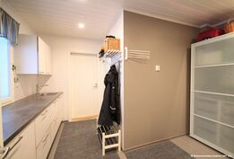 Kodinhoitohuone, jossa laajennustila tekstiilien huoltoon mm. mankeli löytyy lasiliukuovien takaa.