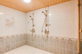Iso kylpyhuone, jossa kaksi suihkua