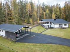 Siporex-kivitalo, asfaltoidut pihat, autotalli ja katokset.