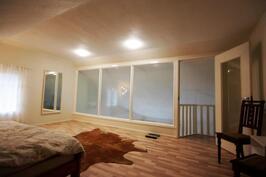 Upea iso makuuhuone yläkerrassa lasi-ikkunoiden kera
