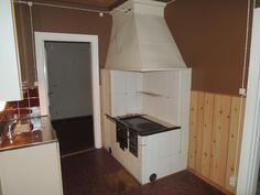Toisessa keittiössä vaalea puuhella.
