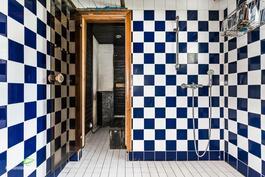 Reilun kokoinen kylpyhuone, jonka jatkeena on