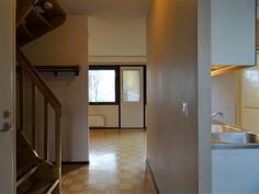 Eteinen, taustalla olohuone, oikealla keittiö.