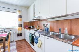 Hyvän kokoinen keittiö, jossa valkoiset kaapistot
