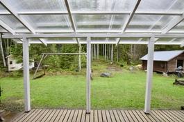 Umpisuojaisella takapihalla valokatettu terassi Länteen
