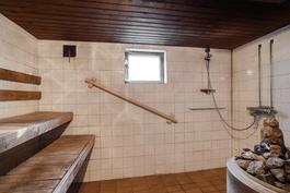 Kellarissa sauna, jossa puilla lämpiävä kiuas/ Trä-äldad bastukamin i bastun.