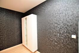Olohuoneen seinään kiinnitetty vitriinikaappi