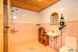 Kylpyhuone on kauniisti laatoitettu.