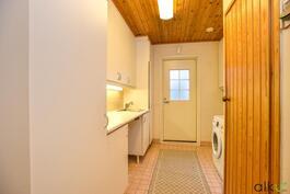 Kodinhoitohuoneessa kaikki tarpeellinen ja käynti takapihalle.