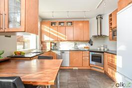 Laadukkaat kodinkoneet kivi- ja puutasojen kera täydentävät keittiön ilmeen.