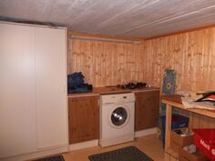 Kellarikerroksen kodinhoitohuoneessa on tilaa pyykin kuivaukseen ja kaappitilaa säilytykseen