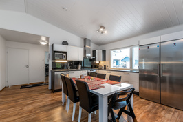 Avara ja tilava keittiö sekä olohuone.
