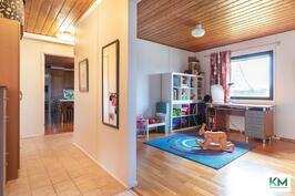 Näkymä makuuhuoneiden 1 ja 2 ovelta monitoimihuoneeseen sekä keittiöön.
