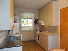Keittiön kaapistoja. Ovi oikealla on pukuhuoneeseen