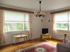 Olohuone on valoisa ja ikkunasta on vesistönäkymä