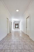 Asuinhuoneet sijaitsevat alakerran pitkän käytävän varrella