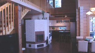Olohuoneen jatkeena tyylikäs ja toimiva keittiö saarekkeella.