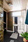 Kylpyhuoneesta tulee luononvalo saunaan lasioven lävitse.