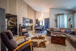 Alakerrassa olohuone, keittiö ja ruokailutila nivoutuvat yhtenäiseksi tilaksi.