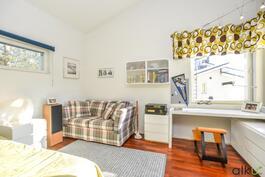 Yläkerran toinen tilava makuuhuone kylpee luonnonvalossa.